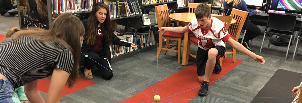 students holding strings to suspend tennis ball in the air