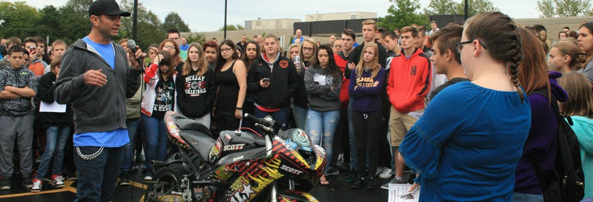 man talking to students grouped around motorcycle