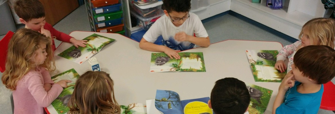 elementary students reading books at table
