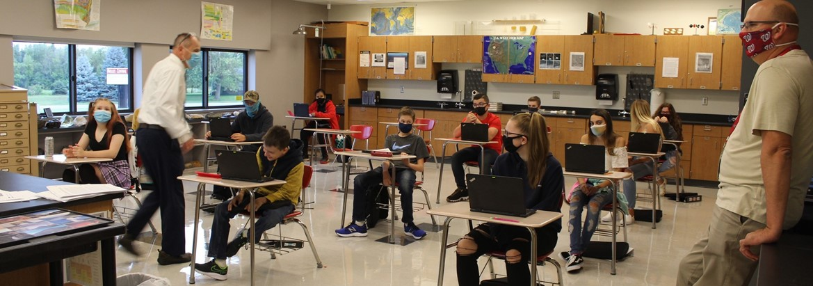 students sitting at desks with laptops