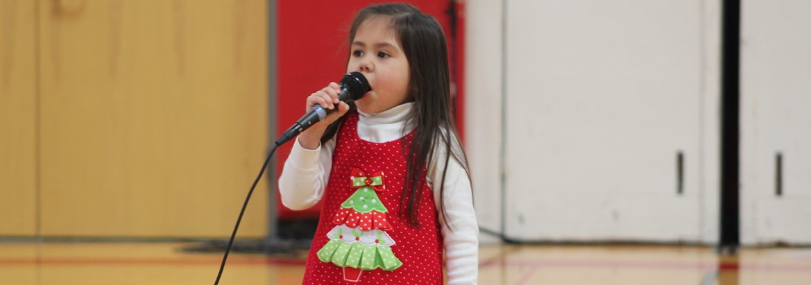 girl in christmas dress singing into microphone