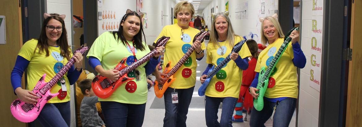 teachers dressed for halloween holding guitars